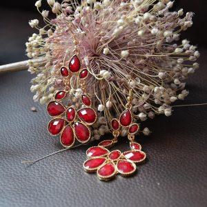 Mooie rode oorbellen in combinatie met goudkleurige omkapseling