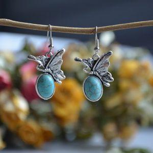 Oorbellen met turquoise kleur steenovaal met mooie vlindertjes erop