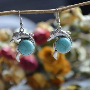 Turquoise oorbellen in de vorm van een dolfijntje